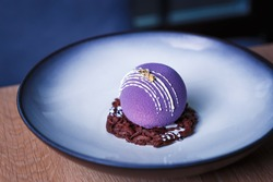 Decorative dessert food.Beautiful purple cake decorated with chocolate swarf served on round plate in Italian restaurant.Delicious desserts,pastry for snack meal.Enjoy desserts cooked in Italy