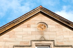 Decorative detail of the facade on the pediment of an old historic building, Roth, Germany.