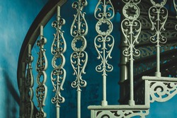 Decorative detailed wrought iron bannister of spiral staircase, oriental style. Architectural details, green copper staircase, beautiful craftsmanship handmade colonial stairs bannister. Teal Indigo