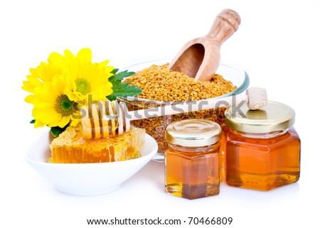Decorative display with jars of fresh honey, a small honeycomb and dipper, and natural flower pollen in the background.