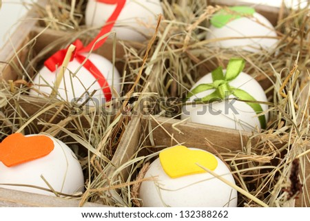 Decorative Easter eggs in wooden basket close up