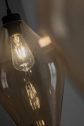 Decorative edison style LED light bulb in a transparent glass chandelier.