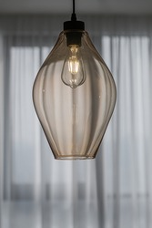 Decorative edison style LED light bulb in a transparent glass chandelier on a window background.