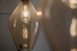 Decorative edison style LED light bulb in a transparent glass chandelier with free space for text on the right.