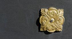 Decorative element of a metal door. Decorative element of a metal fence. Gold decorative element on grey background