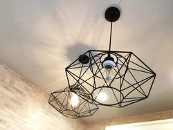 Decorative fixture, light bulb and lamp in modern style hanging from the ceiling on white background. Vintage design.