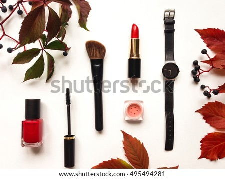 Decorative flat lay composition with cosmetics, woman accessories, decorated with autumn leaves and berries. Flat lay, top view on white background, fashion still-life