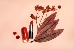 Decorative flat lay composition with cosmetics, woman beauty products, red lipstick, nail polish, decorated with autumn leaves and berries. Flat lay, top view on light background, fashion still life