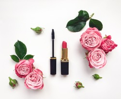 Decorative flat lay composition with lipstick, mascara and flowers. Top view on white background, make up theme