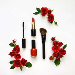 Decorative flat lay composition with woman cosmetics and red rose flowers. Flat lay, top view on white background, make up