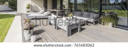 Decorative flowerpots and lanterns on wooden patio on sunny day