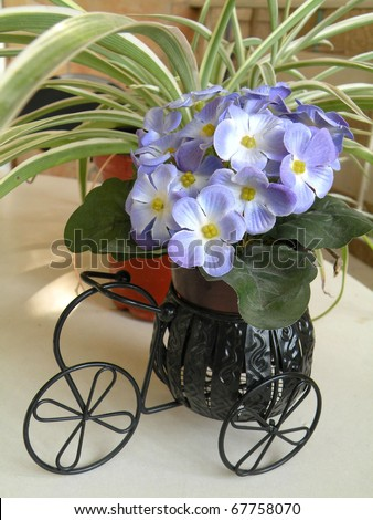 decorative flowers in a decorative supports a carriage on wheels and flowers pots