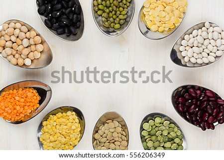 Decorative frame of assortment different beans in  spoons with copy space on white wood background. Top view, closeup. #556206349