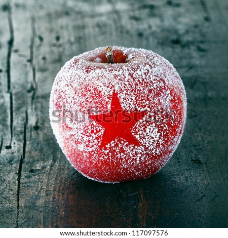 Decorative fresh ripe red Christmas apple frosted with a star pattern on an old vintage wooden table top, closeup in square format