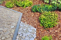 Decorative Garden Design. Backyard Garden Modern Designed Landscaping. Back Yard Lawn And Natural Mulched Border Between Grass, Plants And Pebble, Gravel Or Stone Walk Path.
