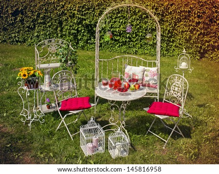 Decorative garden with white furniture and picnic table in the summer.