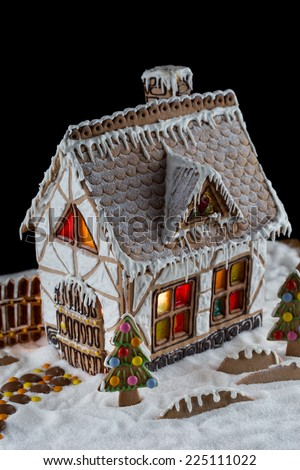 Decorative gingerbread house with lights inside on black background. Rural Christmas night scene