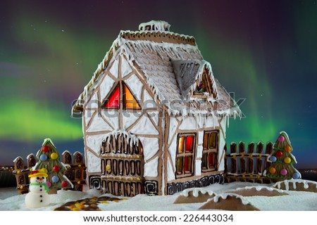 Decorative gingerbread house with lights inside with Northern lights on background. Rural Christmas night scene