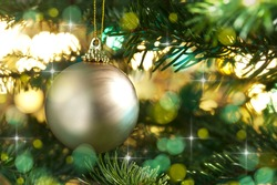 Decorative gold bauble in a Christmas tree in front of a glitter background