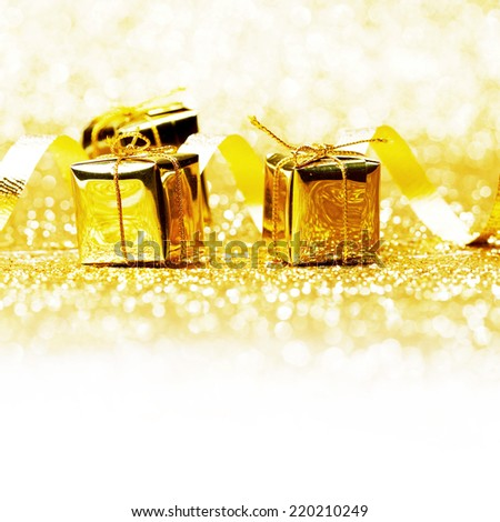 Decorative golden boxes with holiday gifts on shiny glitter background