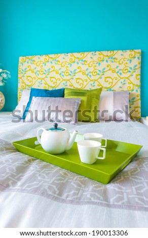 Decorative green color tray with the tea, coffee set on the bed in the luxury master bedroom. Interior design. Vertical.
