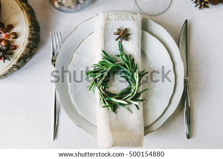 Decorative green wreath on a napkin as a part of table appointments , clean white tablecloth background, top view. Christmas table place setting.