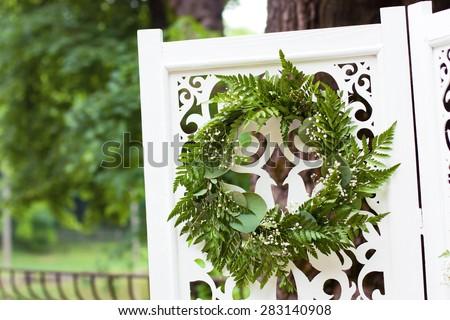 Decorative green wreath on white wooden folding screen as wedding decoration