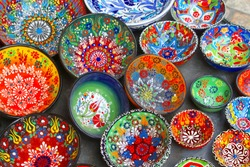 Decorative hand painted ceramic bowls with colorful abstract patterns in arts and crafts store, souk (Shuk) flea market in Middle East