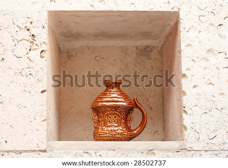 Decorative handmade earthenware in wall niche. Ukrainian culture.