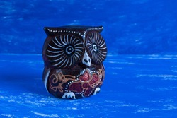Decorative handmade wooden carving statue show brown owl on abstract watercolor background.