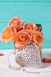 Decorative heart and  fresh roses flowers on white wooden background against  turquoise  wall. Vertical image. Floral still life. Selective focus.
