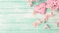 Decorative heart  and  hyacinths flowers  on turquoise painted wooden planks. Selective focus. Place for text. Toned image.