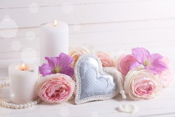 Decorative heart, pink roses  and violet clematis flowers , candles in ray of light  on white  wooden background.  Selective focus. Place for text.