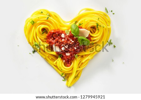 Decorative heart shaped pasta still life formed of cooked spaghetti topped with tomatoes, basil and parmesan cheese