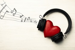 Decorative heart with modern headphones on light background