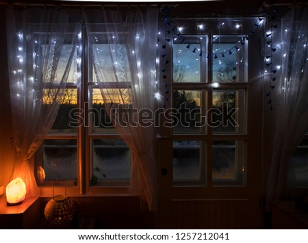 Decorative Himalayan Salt lamp turned on by old white wooden window with white net fabric curtains, looking out the wooden frames window sun setting over the forest in winter. Frosty glass.