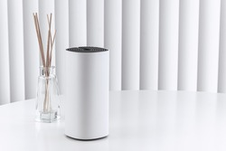 Decorative home WiFi router on white table, vertical blinds.