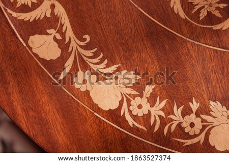 Photo of  Decorative inlay carving on a wooden table, vintage furniture details