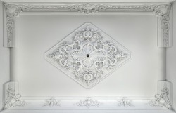 Decorative item made of white plaster on ceiling. Relief stucco interior