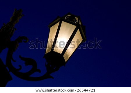 Decorative lamp post photographed in the clear dark blue midnight