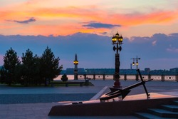 Decorative lamppost with anchor on the square in front of the Volga river bank during sunset with a beautiful colorful sky and an outgoing orange sun. Petrovskaya embankment, Astrakhan, Russia.