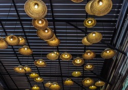 Decorative lamps, made of hats were installed under metal ceiling in open air indoor.