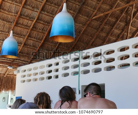 Decorative lanterns under palm roof of service station in tropical resort in a beach area.