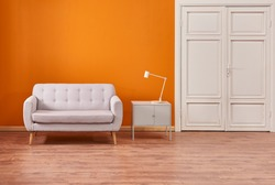 Decorative living room orange wall and furniture decoration in the living room interior style. Brown parquet and grey cabinet style.