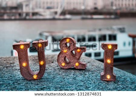 """Decorative luminescent letters saying """"U & I"""" on the background of a river"""
