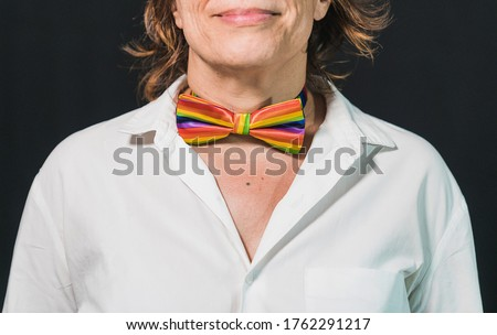 Decorative makeup with a gay pride theme. Gay pride bow tie. Lady's neck with gay pride makeup. Gay pride devices. Rainbow flag. Rainbow flag clothing. Old lady with rainbow flag.