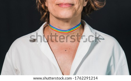 Decorative makeup with a gay pride theme.Gay pride choker. Lady's neck with gay pride makeup. Gay pride devices. Rainbow flag. Rainbow flag clothing. Old lady with rainbow flag.