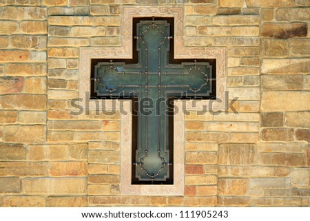 decorative metal cross on textured wall