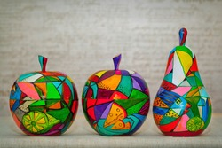 Decorative multi-colored apples and pears. Contemporary art, decorative fruit made of wood, hand painted