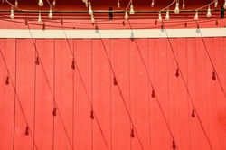 Decorative outdoor light bulbs hanging on wires and its shadow lay on the red wooden barn facade
